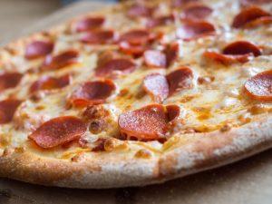 Pizza lying on chopping board